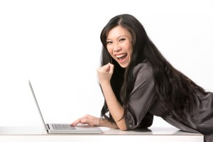 Excited Asian woman using her laptop.